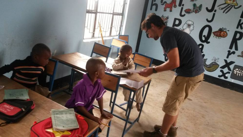 Andrew marks homework at the LK Kindergarten. Boma Africa