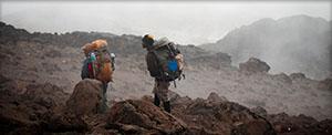 Lau and Thomas hike on a rainy Kilimanjaro.